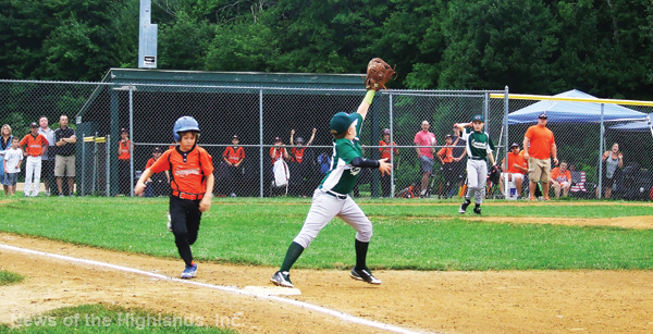 Photo by Ken Cashman First baseman Luciano Fiorello steps on first ahead of a base runner, as the 9-10 boys defeated Montgomery 9-7 on Saturday morning, July 9.