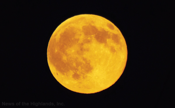 "(Photo by Jason Kaplan) Tuesday night's rising moon had an orange glow due to particles in the atmosphere scattering the light. The July full moon is also known as the ""Buck Moon"" because this month male deer start to grow antlers."