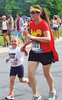 "Photo by Ken Cashman Caitlin and Maeve Sherry (also known as ""Wonder Woman"") finished the Main Street Mile together. Both were smiling."