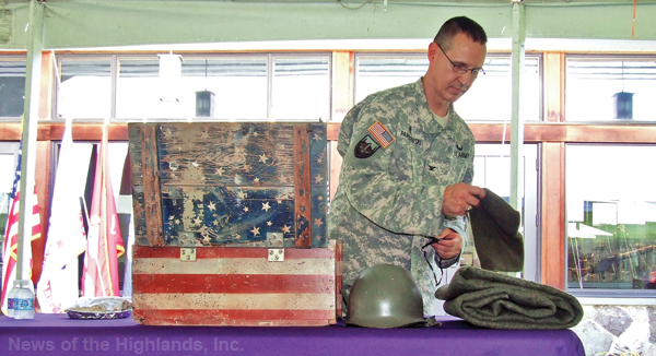 Photo by Ken Cashman Father Matthew Pawlikowski spreads props on a table for his presentation at the Purple Heart Hall of Honor on Aug. 7.