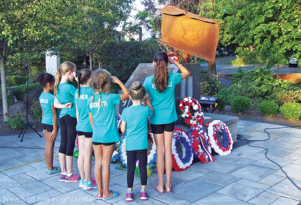Representatives of Gym Kids placed a wreath at the Ken Kumpel 9-11 Monument at Chadeayne Circle.