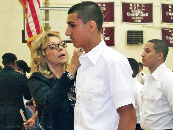 Photo by Ken Cashman Faculty member Susan Pasquale attaches a cadet pin to the lapel of Giorgi Tsiklauri. The pinning was part of a Sept. 24 ceremony in the gymnasium.