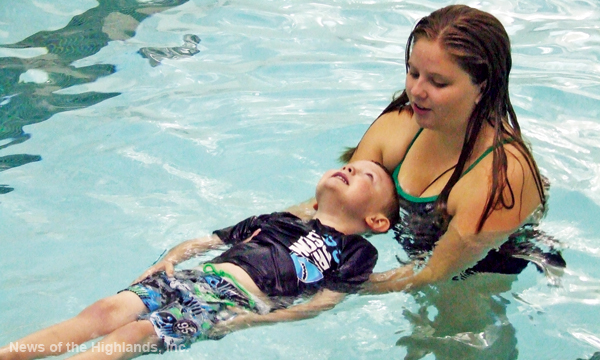 Photo by Jason Kaplan Cornwall High School student Megan Harvey helps Michael Cahill learn how to float. The varsity swimmers are giving lessons to children of military families and emergency personnel.