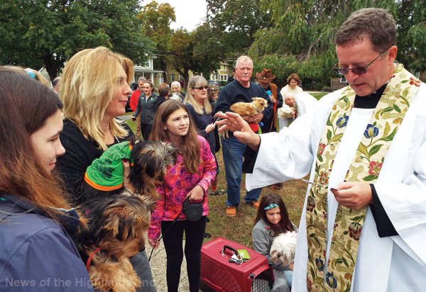 Photo by Jason Kaplan Nearly three dozen animals, including dogs, cats, hamsters, a guinea pig, and even a hermit crab, gathered for the blessing of the pets at St. Thomas of Canterbury Church on Sunday. Rev. Rees Doughty reads a blessing for Moose and Bear.