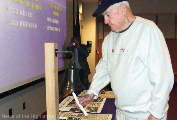Gene Murphy, tolls a bell in honor of those members of the U.S. Marine Corps who died as a result of the attack on Pearl Harbor.