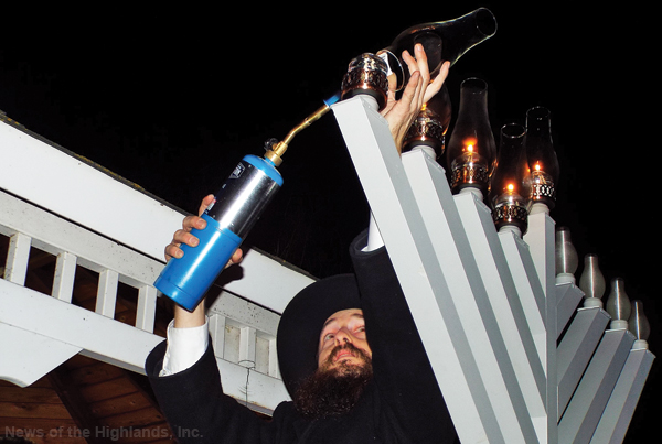 Photo by Jason Kaplan On Tuesday, Rabbi Shmuel Serebryanski lights the menorah, at Rings Pond, on the fourth night of Hanukkah. About a dozen people gathered to hear the story behind the origin of the holiday and why it lasts eight nights. The guests were then invited back to Munger Cottage for donuts and homemade latkes.