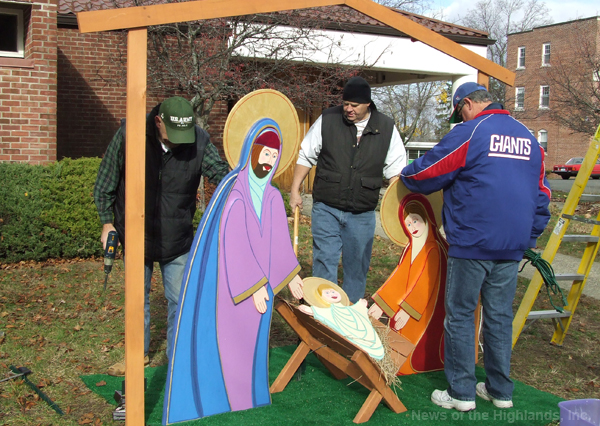 Photo by Jason Kaplan Knights of Columbus members Tom DiSalvo, Sr., Jim Lulves, and Tom Kane, erected the Manger Scene in front of St. Thomas of Canterbury Church last week. They also set up the scene in the Village Square. The pieces were built and designed by Gregory Rocco.