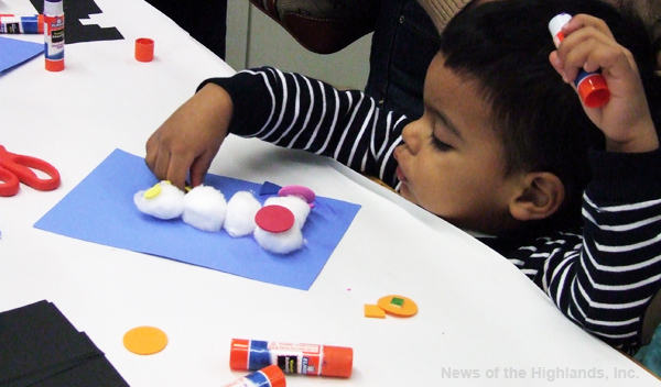 Luishmel Reyes uses cotton balls to make a snowman during the Cornwall Public Library's winter carnival.