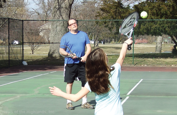 Photo by Jason Kaplan Taking advantage of the 70-degree weather, last week, Manny Lathouris began teaching his daughter, Sasha, how to play tennis. Others took advantage of the spring-like day by playing basketball, riding a bike, walking, or visiting the playground.