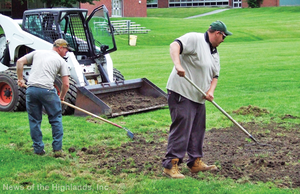 Photo by Jason Kaplan Gary VanVleit and Harvey Barkley, employees in the Cornwall Central School District's Buildings and Grounds Department, put down new soil and seed, on the field adjacent to the middle school, in preparation for the soccer season.