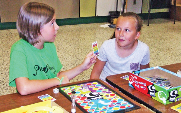 "Photo by Jason Kaplan Town campers were forced to spend Friday indoors due to the threat of thunderstorms. That didn't dampen the kids' spirits, however, as they found other things to do. They played basketball in the gymnasium, watched a movie, or worked on a puzzle. Colby Van Dam and Megan Maffei played a board game called ""Name 5."""