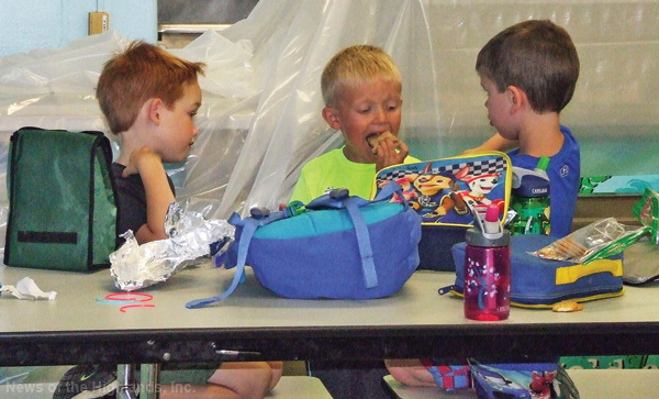 Photo by Jason Kaplan Village campers Ethan Greenblatt, Landon Lavallee, and Noah Chyla palaver while eating lunch.