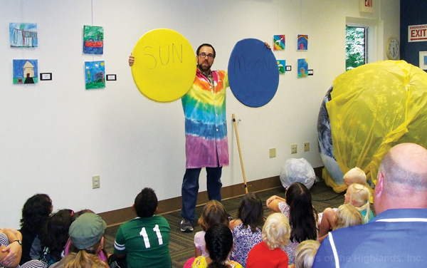 During an Aug. 14 visit to the Cornwall Public Library, Prof. David Kashinski held models of the moon and sun. He explained that the two objects appear to be the same size, because the moon is so much closer to the Earth.