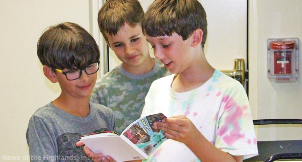 Jasper Haase, J.T. Geraci, and Nicholas Conti peruse the books written and illustrated by their peers.