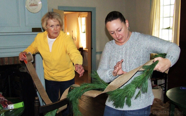 Eileen Tulloch and Colleen Zlock wrap ribbon around some garland as they decorate Sands Ring Homestead for the holiday season.