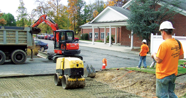 Photo by Jason Kaplan The Cornwall Public Library's parking lot fills quickly when popular programs are held, so 12 new spaces are being added courtesy of a NYS Construction Grant and the library's capital fund. Contractors with Nannini & Callahan Excavating started the project by removing one of the center dividers and expanding the area to be paved. A remote control was used to guide a roller and flatten the dirt.