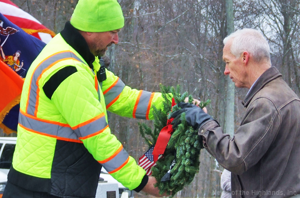Dave Andryshak (left) hands a wreath to Sgt. Major Van Wagner of the Minisink Valley Junior ROTC program. Mr. Andryshak is the superintendent of the Orange County Veterans Memorial Cemetery, where volunteers decorated graves on Dec. 16 in observance of Wreaths Across America.
