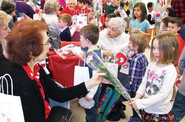 Photo by Jason Kaplan On Tuesday, children from Butterhill Day School entertained seniors at Munger Cottage. They sang Valentine's Day related songs, then handed out flowers and gift bags to each of the elders.